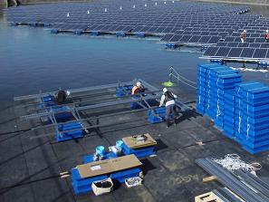フロート式水上太陽光発電システムのユニットを組み立てる作業員