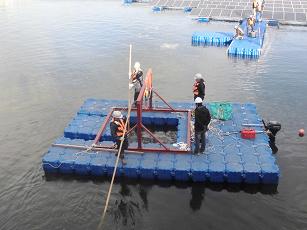 水上で桟橋を組み立てる作業員