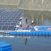 フロート式水上太陽光発電システムのユニットを連結する作業員