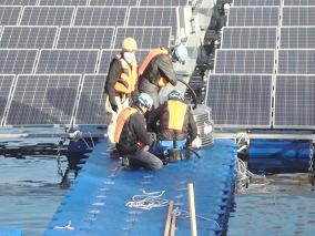 桟橋の上で電気工事を行う作業員