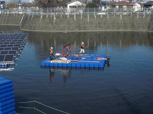 ポンツーン船で水上作業台に戻る作業員