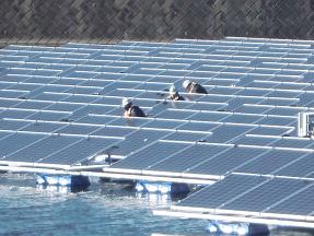 フロート式水上太陽光パネル間の配線をする作業員