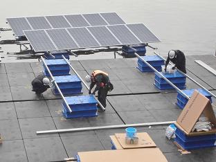 水上太陽光発電システムのユニットを組み立てる作業