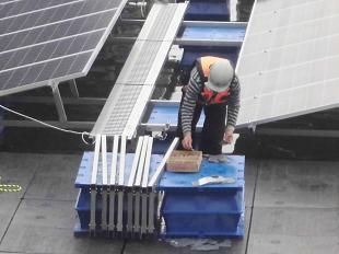水上太陽光システムの架台を組み立てる作業員